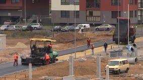 Los trabajadores con la extensión de la máquina ponen el asfalto en emplazamiento de la obra almacen de metraje de vídeo