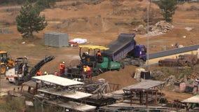Los trabajadores con la extensión de las máquinas ponen el asfalto en emplazamiento de la obra almacen de video