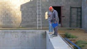 Los trabajadores constructivos en un casco discuten casas del edificio de la construcción con una piscina metrajes
