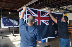 Los trabajadores cuelgan una impresión de la bandera nacional de Nueva Zelanda Fotografía de archivo