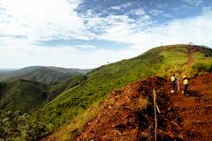 Los trabajadores de construcción de la explotación minera que examinan la montaña rematan en África Imagenes de archivo
