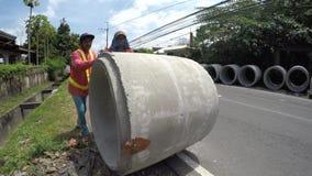 Los trabajadores de construcción empujan la alcantarilla grande rodante en la carretera almacen de video