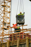Los trabajadores de construcción en hormigón colado del tejado bajaron de una grúa Imagen de archivo libre de regalías