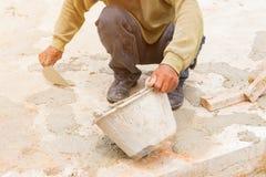 los trabajadores de construcción enyesaban el piso de la reparación en estructura del lugar de trabajo una casa foto de archivo