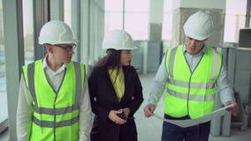 Los trabajadores de construcción, equipo del negocio del trabajo en equipo 4 k discuten un diseño arquitectónico metrajes