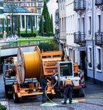 Los trabajadores de construcción hacen reparación la ingeniería urbana Reemplazo del cable que pone la comunicación óptica modern Foto de archivo libre de regalías