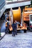 Los trabajadores de construcción hacen reparación la ingeniería urbana Reemplazo del cable que pone la comunicación óptica modern Fotografía de archivo libre de regalías