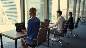 Los trabajadores de la atención al cliente están trabajando en centro de atención telefónica de la atención al cliente almacen de video
