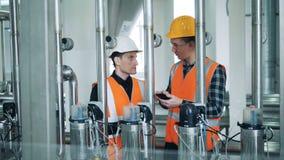 Los trabajadores de la cervecería están regulando el equipo y hablar metrajes