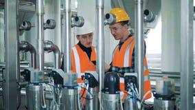 Los trabajadores de sexo masculino miran el equipo de la cervecería, cierre para arriba almacen de video