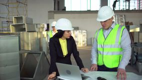 Los trabajadores de sexo masculino y de sexo femenino del almacén están mirando un ordenador portátil y están discutiendo la logí metrajes