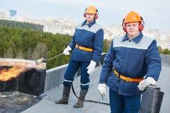 Los trabajadores de tejado plano con la techumbre del betún sentían y la antorcha de la llama imagenes de archivo
