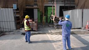 Los trabajadores del área del edificio de la calle ayudan al haz del metal de la elevación de la grúa almacen de metraje de vídeo
