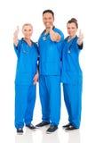 Los trabajadores del cuidado médico manosean con los dedos para arriba foto de archivo libre de regalías