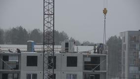 Los trabajadores del emplazamiento de la obra construyen la casa de bloque en invierno Caída de la nieve almacen de metraje de vídeo