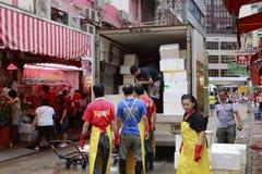 Los trabajadores descargan la comida del camión refrigerado Imagenes de archivo