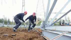 Los trabajadores en cascos rojos tuercen el tornillo de la ayuda con la herramienta metrajes