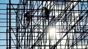 Los trabajadores en los constructores de la puesta del sol montan diseño Siluetas del trabajador del ingeniero de los hombres en  metrajes