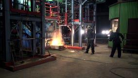 Los trabajadores en desgaste protector actúan en el horno de la fusión del metal metrajes