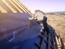 Los trabajadores en el tejado de la casa instalan una pel?cula impermeable debajo del tejado y la aseguran con una grapadora imagen de archivo libre de regalías