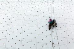 Los trabajadores en el tejado del edificio substituyen las luces LED foto de archivo