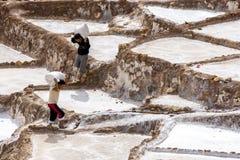 Los trabajadores en la evaporación de la sal de Maras acumulan en Perú Foto de archivo libre de regalías