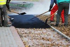 Los trabajadores están nivelando la miga del asfalto en el hoyo con un fricción-rodillo antes de pavimentar con un mini rodillo d fotos de archivo libres de regalías