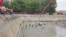 Los trabajadores están separando el hormigón sobre piso reforzado grande en el emplazamiento de la obra almacen de metraje de vídeo