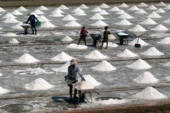 Los trabajadores están trabajando en una granja de la sal en Tailandia Foto de archivo