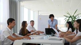 Los trabajadores hablan del nuevo desarrollo de negocios de las ideas que se sienta en la tabla grande en oficina moderna almacen de video