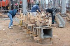 Los trabajadores hacen que la columna encajona y que guarda al lado de la grúa para la columna construida imagenes de archivo