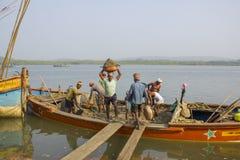 Los trabajadores indios de los hombres descargan el barco con la arena por el trabajo manual en el fondo del río lleve imagenes de archivo