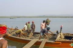 Los trabajadores indios de los hombres descargan el barco con la arena por el trabajo manual en el fondo del r?o fotos de archivo