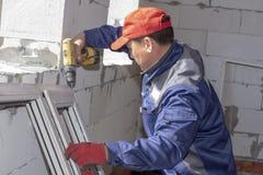 Los trabajadores instalan el satinado en una casa bajo construcci?n imagen de archivo