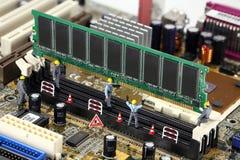 Los trabajadores instalan RAM en la PC Foto de archivo