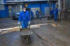 Los trabajadores limpian un distrito de la fábrica después de desastre Imagen de archivo libre de regalías
