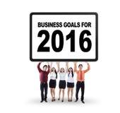 Los trabajadores llevan a cabo un cartel con las metas de negocio para 2016 Fotografía de archivo