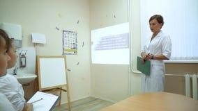 Los trabajadores médicos recolectaron en la oficina para una presentación El médico principal de la institución médica habla a almacen de metraje de vídeo