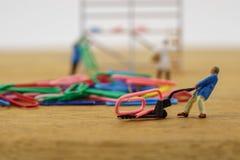 Los trabajadores miniatura del juguete llevan un clip de papel fotografía de archivo libre de regalías