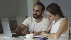 Los trabajadores multiétnicos jovenes en un creativo comienzan para arriba el trabajo almacen de video