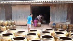 Los trabajadores que ruedan el dragón diseñan los tarros fuera del horno en industria de la cerámica en la provincia de Ratchabur almacen de video