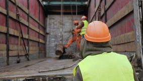 Los trabajadores que usan una grúa descargan un paquete de barras de acero metrajes