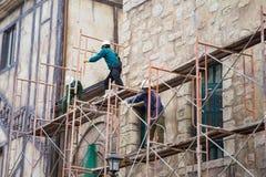 Los trabajadores sin la protección ceñen fijo en andamio en el emplazamiento de la obra foto de archivo libre de regalías