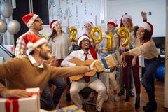 Los trabajadores sonrientes del negocio tienen la diversión y baile en el sombrero de Papá Noel en los regalos de la fiesta de Na fotografía de archivo