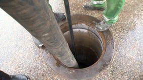 Los trabajadores utilizan las mangueras especiales para bombear de las heces de las aguas residuales de la boca bien metrajes