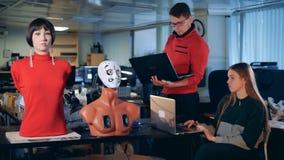 Los trabajadores utilizan los ordenadores portátiles para controlar los robots, cierre para arriba almacen de metraje de vídeo