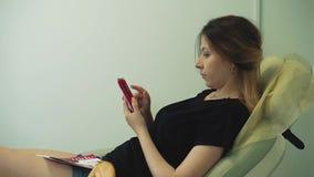 Los trabajos bonitos jovenes de la muchacha sobre el smartphone, miran, leen almacen de metraje de vídeo