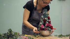 Los trabajos del florista con la composición floral explican técnica en la tabla dentro almacen de metraje de vídeo