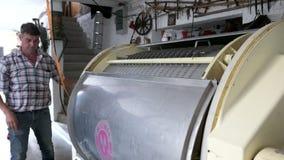 los trabajos del granjero sobre una máquina de la prensa de vino a extraer el vino blanco bostezan almacen de video