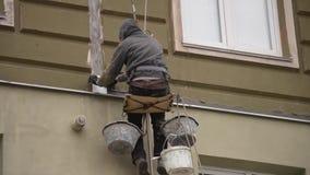 Los trabajos del hombre sobre alta subida trabajan el revestimiento, enyesado de la casa almacen de video